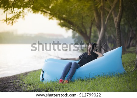 asian woman relaxing in the beautiful park and sitting on her air bed near by the pond