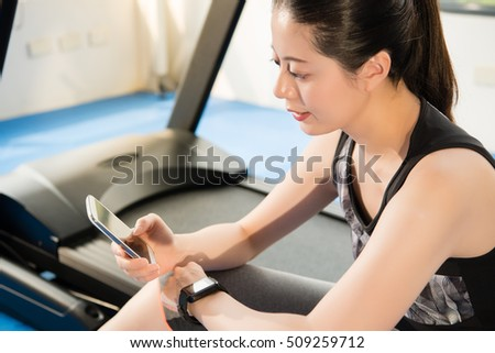asian woman rest sitting on treadmill use smartphone and smartwatch. indoors gym background. health sport concept