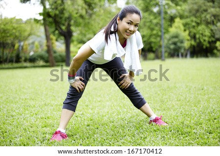 Asian Woman Resting After Exercising In Park - stock photo