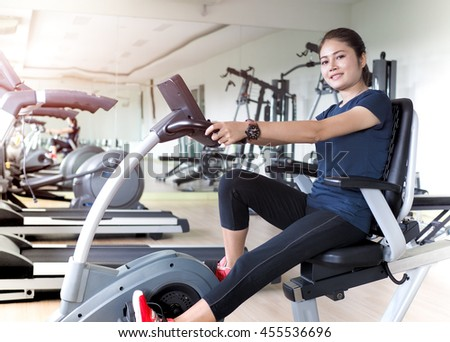 Asian woman riding stationary bike in gym. - stock photo