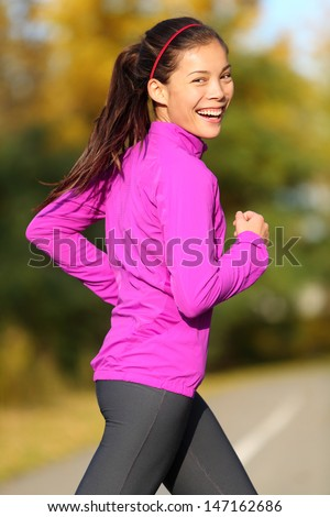 Asian woman running - female runner in autumn forest fall foliage colors. Jogging fit sports fitness girl smiling laughing happy looking at camera. Beautiful energetic mixed race Asian Caucasian model - stock photo