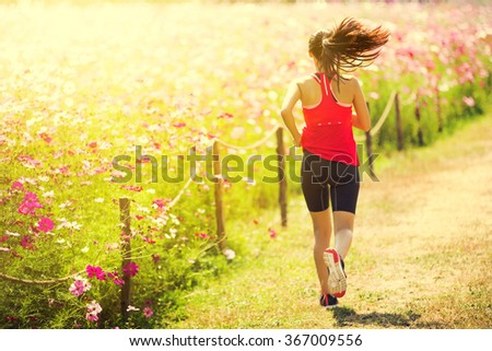 Asian woman running on beautiful flower garden. Her morning exercise  - stock photo