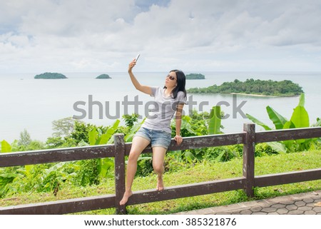 asian woman selfie with seascape against blue sky - stock photo