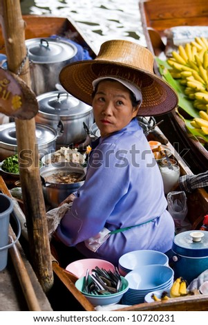 Asian woman selling goods at a traditional Asian floating market near Bangkok, Thailand. - stock photo