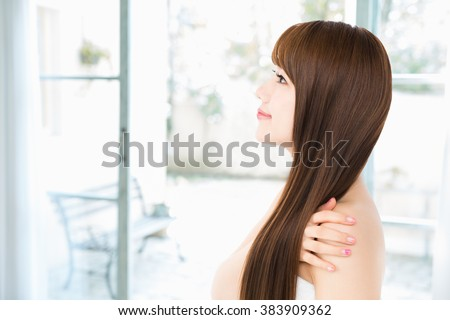 Asian woman showing perfect skin and long hair - stock photo
