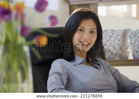 Asian woman sitting in chair - stock photo