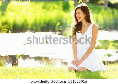 Asian woman sitting in park in spring or summer. Beautiful young woman smiling happy wearing white sundress sitting down in grass in park, Cute mixed race Asian Caucasian woman in her 20s. - stock photo