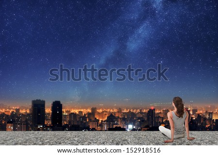 Asian woman sitting on roof, back to camera, and looking on the night city under starry sky. - stock photo