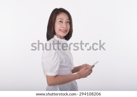 Asian woman sitting on white chair using mobile phone  - stock photo