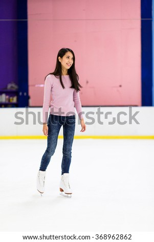 Asian woman skating on ice rink - stock photo