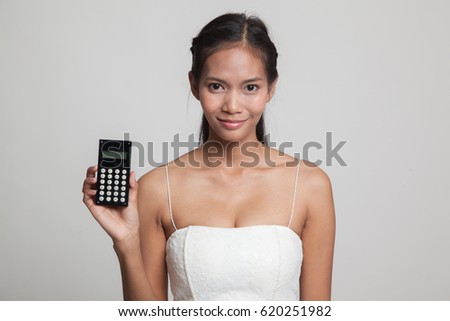 Asian woman smile with calculator  on gray background