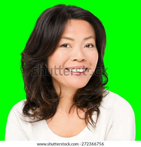 Asian woman smiling happy portrait. Beautiful mature middle aged Chinese Asian woman closeup beauty portrait isolated cutout on green chroma key background.