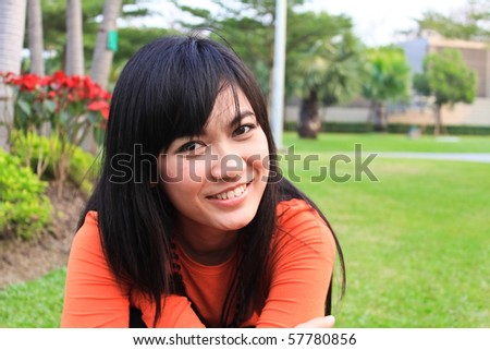 asian woman smiling in the park - stock photo