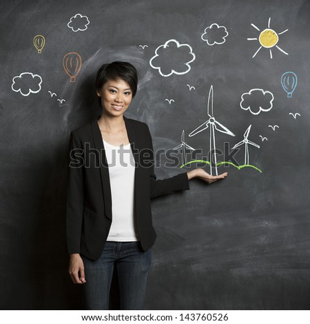 Asian woman standing in front of eco environment sketch on chalkboard. - stock photo