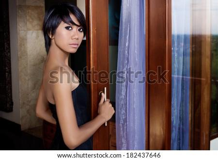 Asian woman stands near the sliding door, bare shoulders and back. reflected in the island of Bali and the bay - stock photo