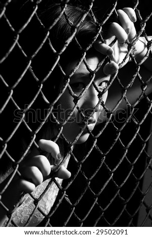 asian woman staring fiercely through fence - stock photo