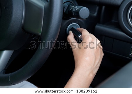asian woman starting the car. - stock photo