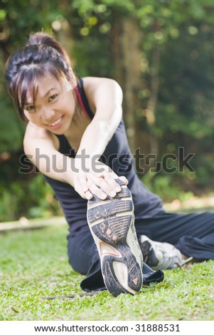 asian woman stretching her leg muscles with a smile - stock photo