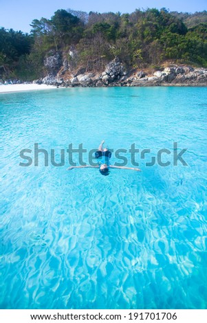 Asian woman swimming in the ocean. - stock photo