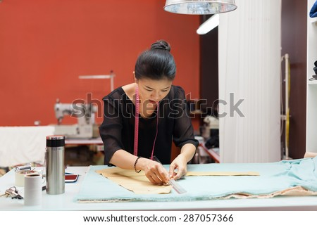 Asian woman tailor fashion clothes dress designer working with fabric on table - stock photo