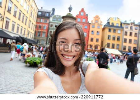 Asian woman taking self portrait selfie photo on Europe travel. Happy candid tourist on Stortorget, big square, Gamla Stan, the old town of Stockholm, Sweden. - stock photo