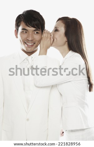 Asian woman telling secret to co-worker - stock photo