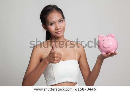 Asian woman thumbs up with pig coin bank  on gray background