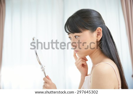 Asian woman to see a mirror - stock photo