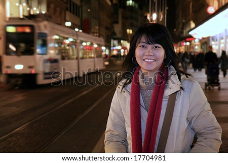 Asian woman traveler walking along the sidewalk of Geneva's shopping district in Switzerland at night.