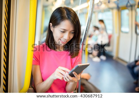 Asian Woman use of mobile phone inside train