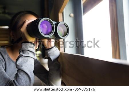 Asian woman use of the binoculars for birdwatching - stock photo