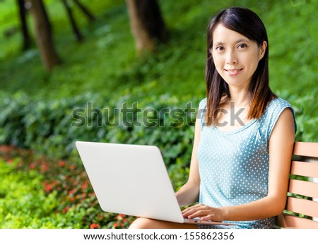 Asian woman using laptop at outdoor