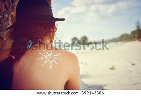 Asian woman using sunscreen skin care cream for sun protection in summer beach lifestyle - stock photo