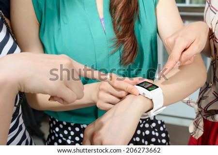Asian woman using wearable watch and showing to her friends. - stock photo