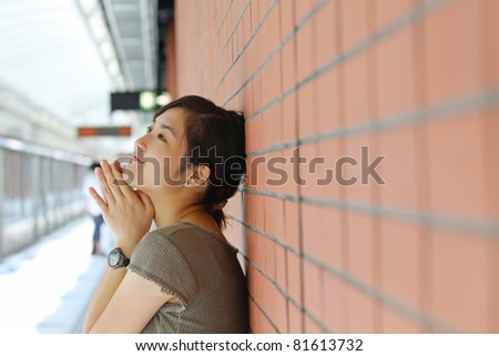Asian woman waiting for train with smile - stock photo