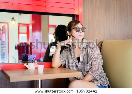 Asian woman waiting in a coffee shop - stock photo