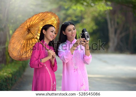 Asian woman wearing a dress of Vietnamese Ao dai is carrying a camera.