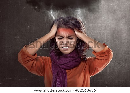 Asian woman wearing scarf looking sick. She has headache