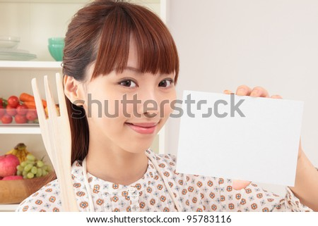 Asian woman with an empty card in the kitchen - stock photo