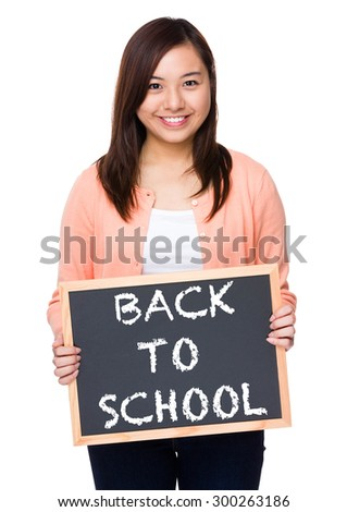 Asian woman with black board showing phrase of back to school - stock photo