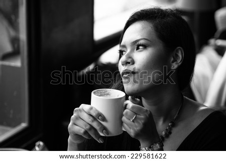 Asian  woman with cup of coffee black and white photo - stock photo