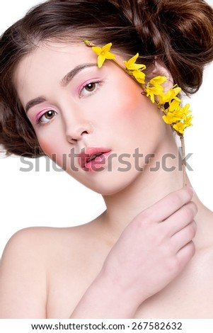 Asian woman with forsythia flower. Beautiful attractive mixed race Chinese Asian / Caucasian female model with perfect skin and pink make up - stock photo