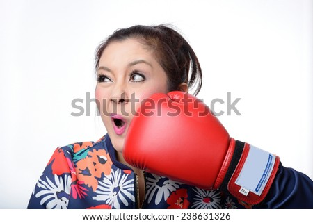 asian woman with red boxing glove punch her face on white background - stock photo