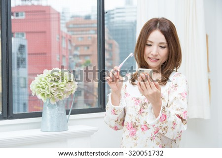 Asian woman with toothbrush and phone
