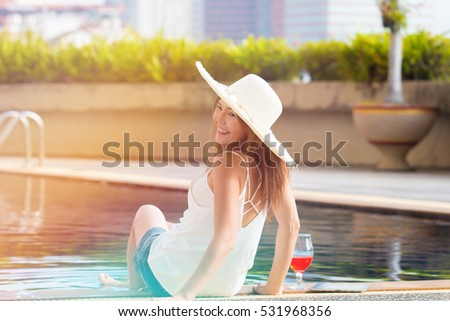 Asian woman with white large summer hat sitting on white pool be