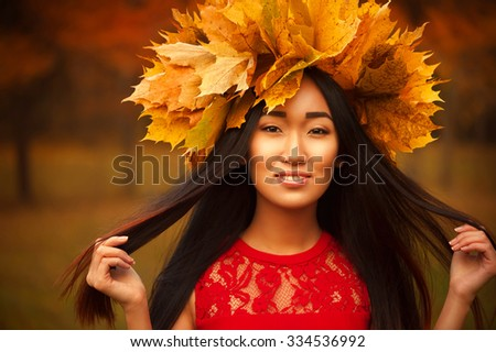Asian woman with wreath of maple leaves - stock photo