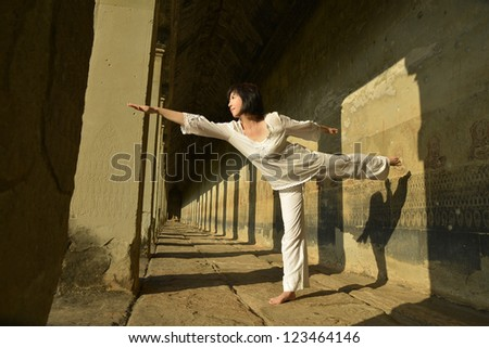 asian woman with yoga pose in ancient corridor - stock photo
