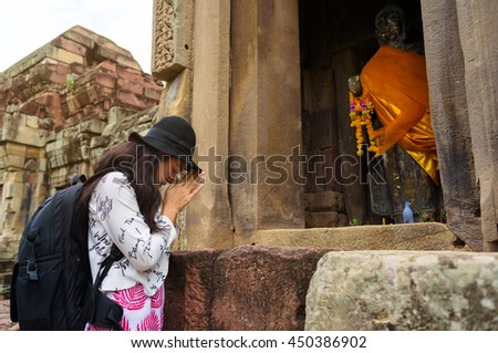 Asian woman worships hands with buddha statue at ancient in Thailand