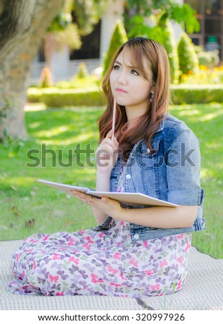 Asian Woman Write a book in the park
