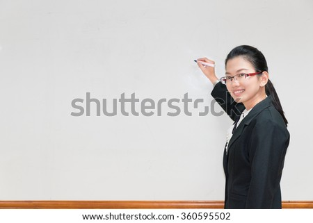 Asian woman writing something in whiteboard with pen and explaining - stock photo